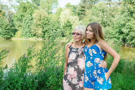 two generations: Two women of different generations are near a pond in the summer. Mother and daughter hugging. Grandmother and granddaughter. Stock Photo