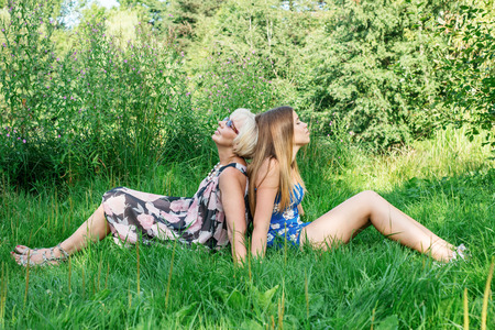 two generations: Two women of different generations sitting on the grass. Mother and daughter Stock Photo