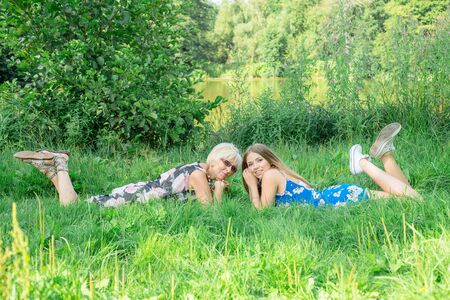 Two women of different generations lie on the grass. Mother and daughter. Grandmother and granddaughter photo