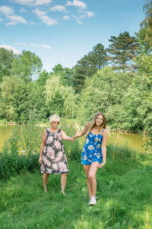 Girl pulls her hand woman. Mother and daughter walking. Grandmother and granddaughter. photo