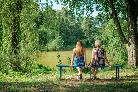Two women of different generations sitting on a bench near a pond in the summer. Mother and daughter hugging. Grandmother and granddaughter.