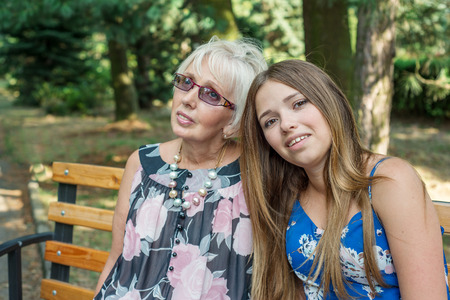Two women of different generations sitting on a bench in the summer. Mother and daughter. Grandmother and granddaughter. photo