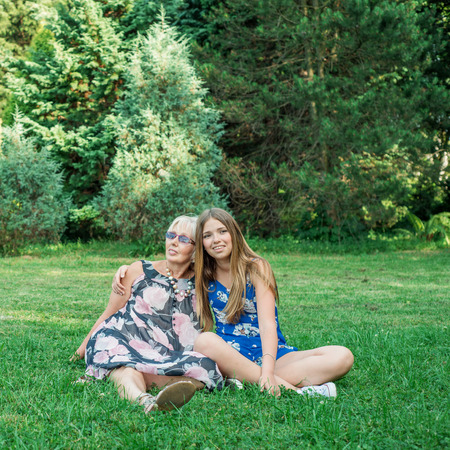 two generations: Two women of different generations sitting on the grass in the park. Mother and daughter. Grandmother and granddaughter.