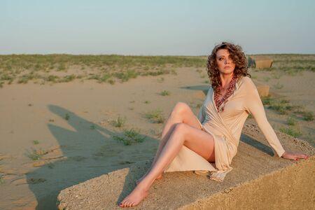 mujeres morenas: Hermosa mujer sentada en una roca Foto de archivo