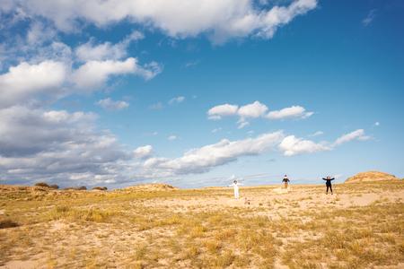 teen golf: Paisaje con la gente. Tres personas de pie en un campo en las rocas con los brazos levantados