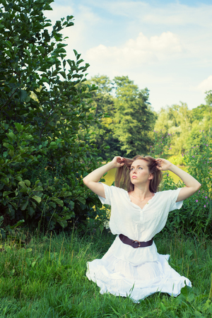 Haired young woman with long hair sitting on the grass back to