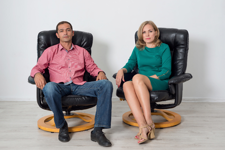 Man and woman sitting on leather chairs in the studio
