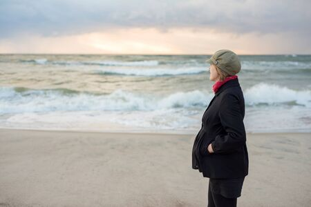 Pregnant woman in a coat walks by the sea Stock Photo