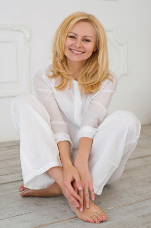 Beautiful blonde woman sitting on the floor in a bright dress and smiling