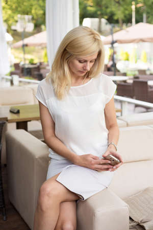 Beautiful blonde woman is sitting in a cafe and talking on the phone Stock Photo