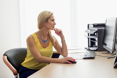 Woman works in the office at the computer Stock Photo