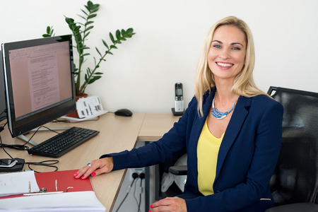 Blonde woman is sitting at the table and smiling