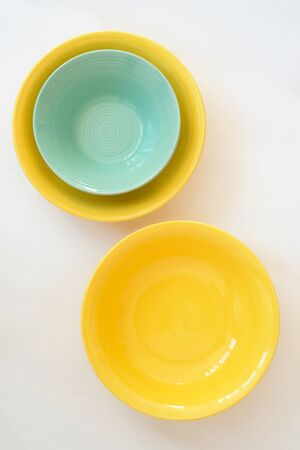 Yellow and turquoise deep plate on a white background 写真素材 - 131995030