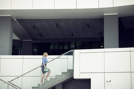 Blonde woman walks the stairs of a public building with a digital tablet