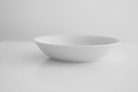 White plate stands on a white table