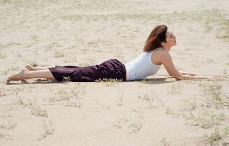Young brunette woman lies on the sand