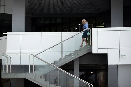 Blonde woman walks down the stairs of a public building