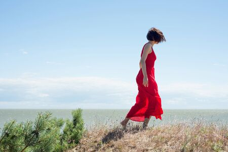 Young brunette woman in a red dress walking on a mountainside Stock Photo