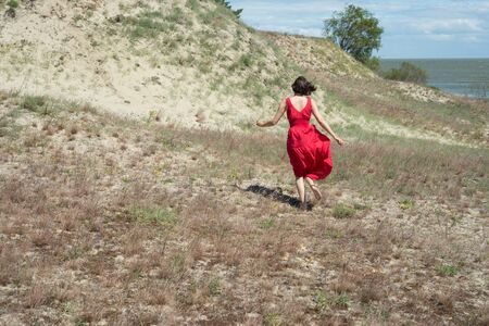 Young brunette woman in red dress runs across the field