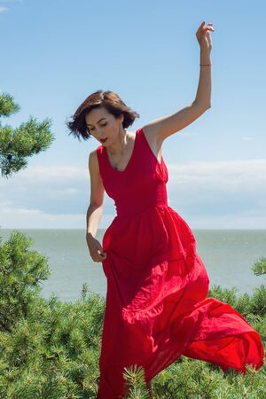 Young brunette woman in red dress near green pine and sea