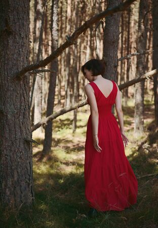 Young brunette woman in red dress walking in the forest Stock Photo
