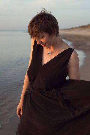 Natural portrait of a woman with a short haircut on the beach