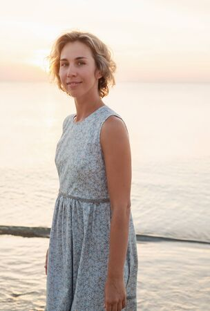 Natural portrait of a blonde woman in a dress near the sea Stock Photo