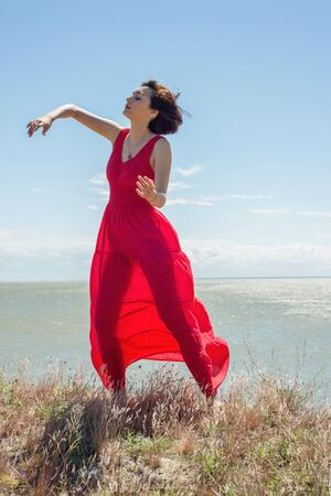 Brunette woman in a red dress is dancing in the nature Stock Photo