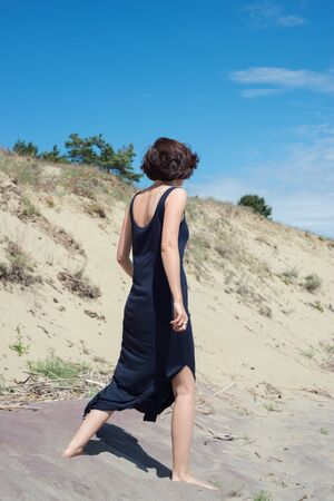 Young brunette woman in dress walking along the seashore Stock Photo
