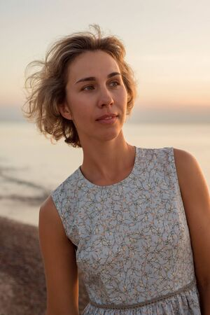 Natural portrait of a beautiful blond woman in a dress near the sea