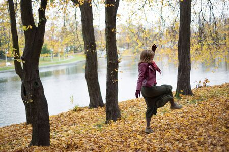 Woman is dancing in the autumn in the park