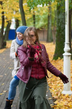 Two women are dancing in the park in autumn Stock Photo