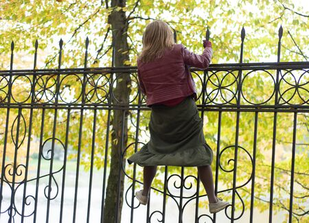 Woman climbs onto an iron fence in the park Stock Photo