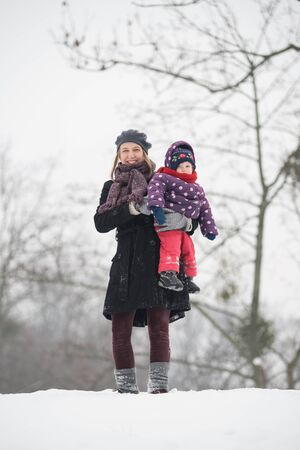Woman carries a child in the winter in the park