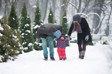 Family with a small child walk in the park in winter Stock Photo