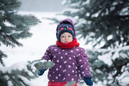 Little girl is standing near the tree in winter