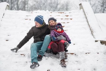 Mom, Dad and Daughter are having a fun winter walk in the park