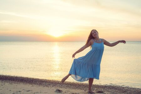 Woman with long hair in a dress dancing near the sea Stock Photo