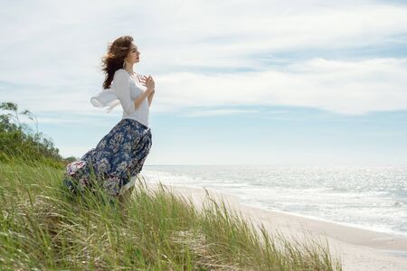 Young brunette woman in dress stands by the sea
