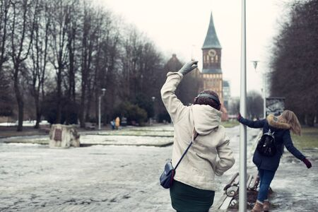 Two women dancing in the park in winter