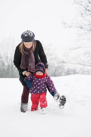 Mom walks with her little daughter in the winter in the snow, first steps Stock Photo