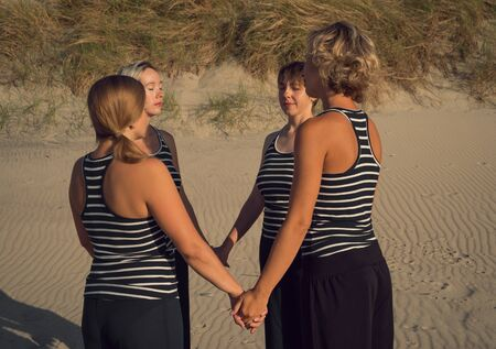 Four women stand in a circle and hold hands on the beach