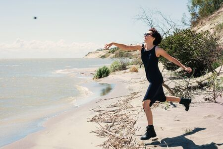 Young woman throws stones at sea Stock Photo