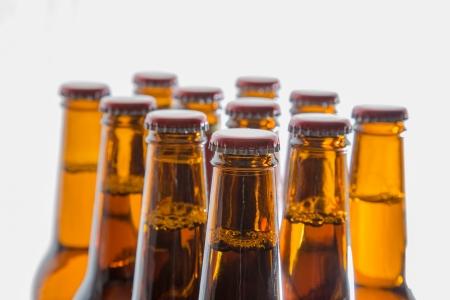 brown bottle: The necks and tops  caps  of full beer bottles