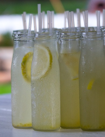 Plenty of glass bottles with ginger beer and lemon slices in it  Straws sticking out on top
