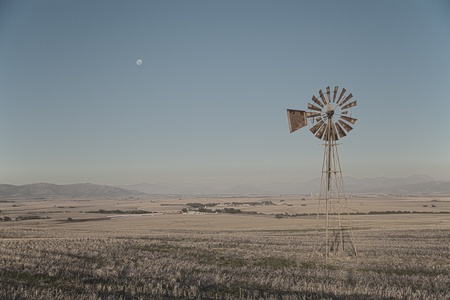 south africa soil: A country side landscape with a wind pump in the middle of dry fields and the moon in the sky