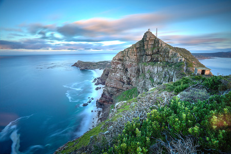 cape: Cape Point, South Africa as time stands still - slight movement in the water and clouds as the sun rises in the back  There Stock Photo