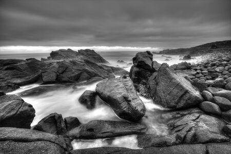 A black and white stormy seascape with big rocks and moving sea water  Dark rain clouds hanging in the sky  Stock Photo
