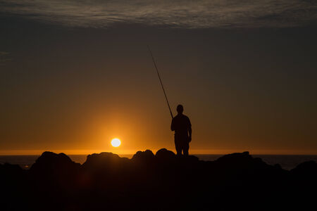 The silhouette of fisherman standing with his fishing rod on the rocks in the sunset, catching fish from the side