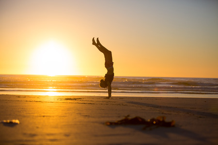 breaking in: A woman doing a handstand on the beach at sunset. Waves breaking in the ocean.